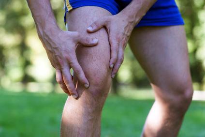 Rehabilitacja ortopedyczna, mężczyzna trzymający się za kolano jako metafora bólu miejscowego