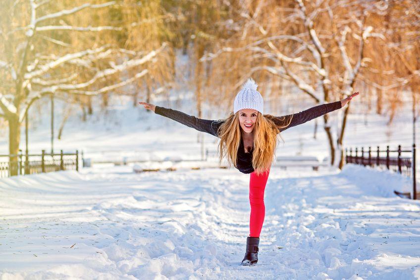 Kobieta ćwiczy jogę w zimowym otoczeniu
